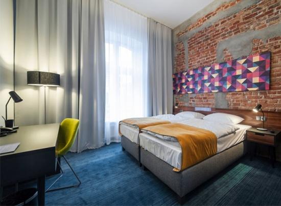 Dormitor cu perete din caramida si mocheta albastra moderna