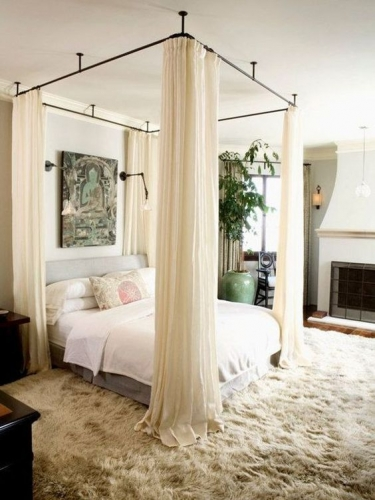 Dormitor cu semineu pat cu baldachin si mocheta pufoasa bej