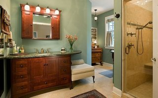 Mobilier pentru baie din lemn tratat culoare nuc asortat cu pereti verzi si pardoseala crem