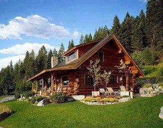 Casa din lemn cu acoperis in doua ape prelungit peste terasa