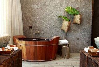 Stil industrial de amenajare a unei bai cu peretii din ciment brut si cada de lemn stil ciubar