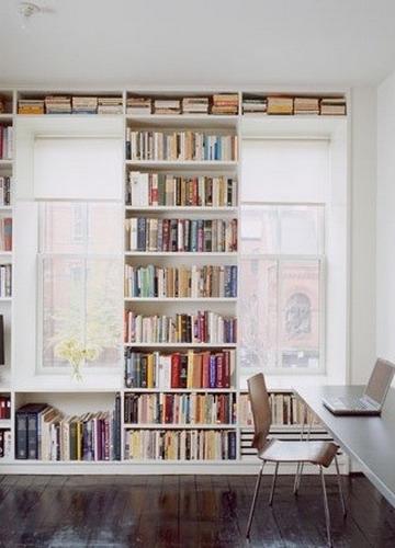 Biblioteca construita pe intreg peretele in jurul ferestrelor