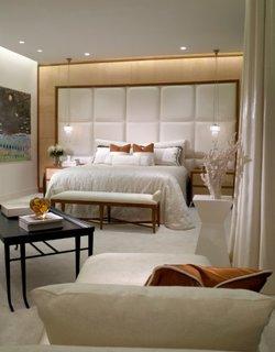 Dormitor cu perete de accent capitonat cu perne albe si suspensii lungi langa pat