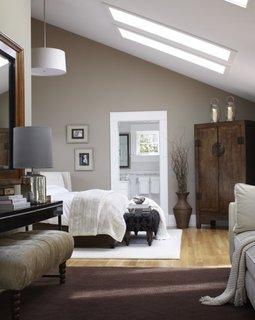 Dormitor la mansarda cu pereti crem si lustra suspendata bu abajur alb