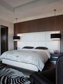 Dormitor negru cu alb si lustre suspendate lungi asezate in lateralele patului