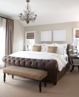 Lustra cu becuri lumanare pentru un dormitor crem cu pat maro inchis