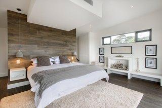 Suspensii albe in dormitor cu perete placat cu lemn
