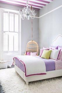 Tavan cu tapet in dungi covor shaggy alb si obloane de lemn pe interior o camera moderna