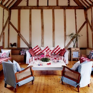 Living rustic cu fotolii cu brate din lemn si ratan si huse textile
