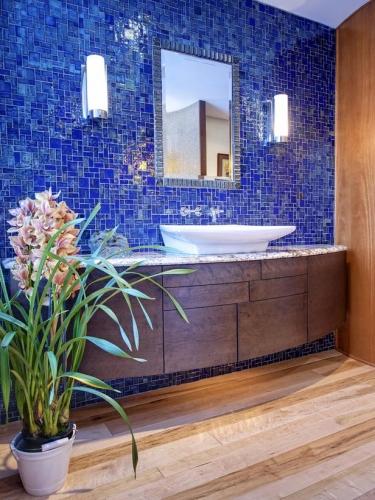 Baie cu perete placat cu faianta albastru turcoaz si mobila din lemn