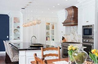 Bucatarie cu mobilier alb si hota din alama facuta pe comanda