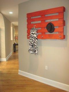 Palet vopsit cu portocaliu atasat pe perete ca si cuier