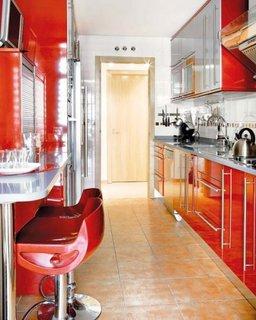 Bucatarie cu mobila rosie si cu masa gen bar