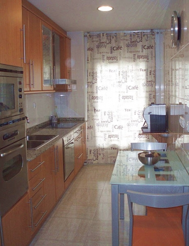 Bucatarie mica si ingusta de apartament cu masa dreptunghiulara ingusta lipita de perete
