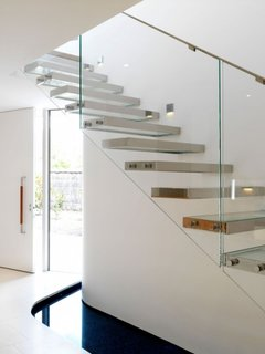 Scara de interior cu trepte pe cadru metalic si sticla si balustrada de sticla