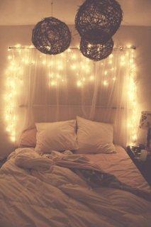 Atmosfera romantica intr-un dormitor cu luminite decorative si materiale textile pe perete
