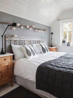 Dormitor cu noptiera din lemn si ghirlanda de LED-uri deasupra patului