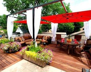 Terasa cu umbrele mari rosii si perdele albe