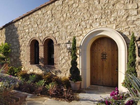 Casa fara etaj cu fatada placata cu piatra si usa mare din lemn masiv si elemente decorative din fie