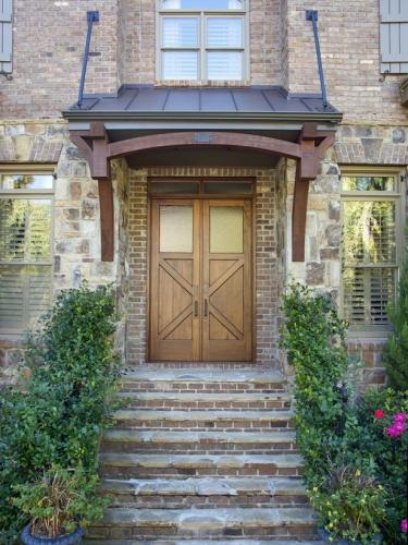 Casa placata cu caramida rosie si usa dubla din lemn masiv la intrare