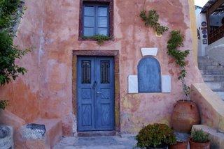 Usa albastra din lemn la o casa cu fatada maro