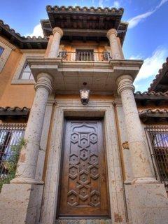 Usa de exterior cioplita in lemn masiv la o casa in stil toscan cu coloane de piatra