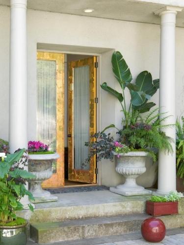 Usa de exterior cu rama aurie si geam mare la o casa in stil mediteranean