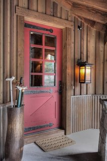 Usa din lemn vopsit maro rosiatic la o casa placata cu lemn