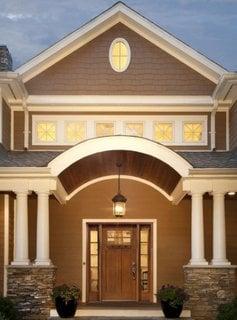 Usa mare din lemn si geamuri pe lateral pentru o casa cu intrare in arcada