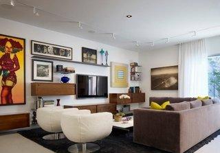 Televizor pe perete incadrat intre tablouri