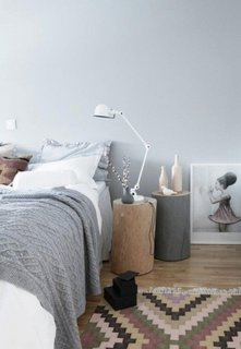 Dormitor amenajat in stil scandinav cu busteni de copac ca si noptiere