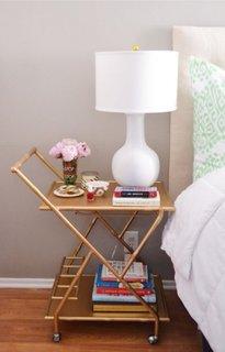 Masuta mobila pentru cafea asezata in dreptul patului