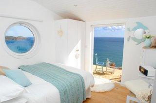 Dormitor mic alb cu vedere catre mare