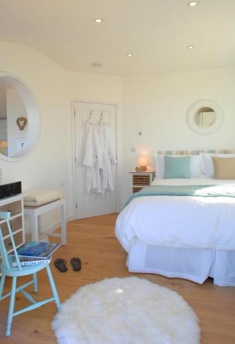 Dormitor mic cu pardoseala de lemn si mobila si pereti albi