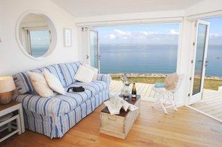 Living cu pardoseala din lemn pereti albi si canapea cu accente turcoaz