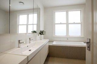 Baie simpla ingusta cu mobilier alb si oglinzi pe tot peretele si cada placata cu gresie