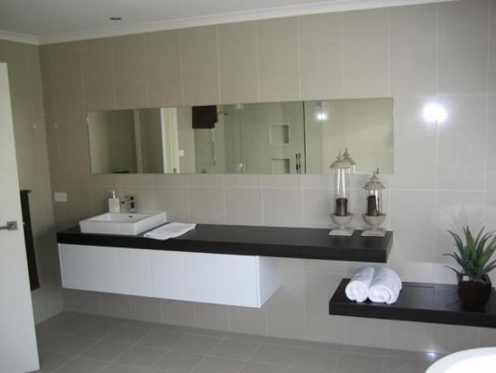 Chiuveta mica de baie asezata pe blat cu dulap suspendat si oglinda ingusta si lunga