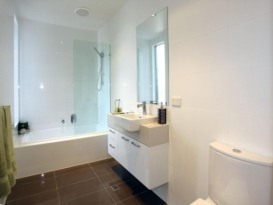 Idee de amenajare baie ingusta cu gresie maro inchis si dulap alb cu chiuveta mica si oglinda simpla