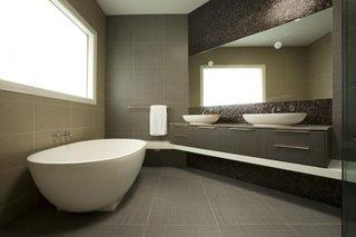 Oglinda dreptunghiulara ingusta aplicata pe perete de baie placat cu mozaic negru