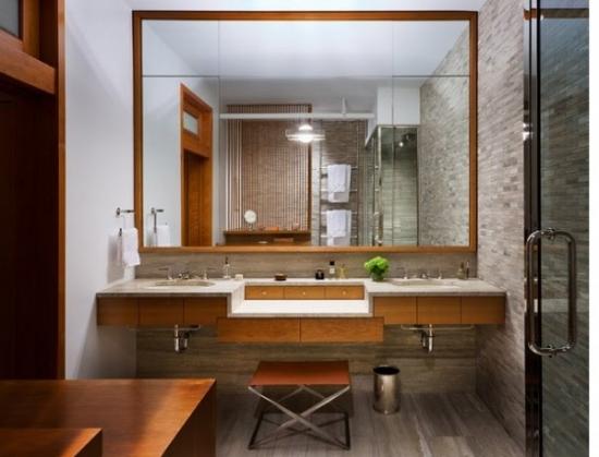 Oglinda mare cu rama de lemn aplicata pe tot peretele din spatele chiuvetei de baie