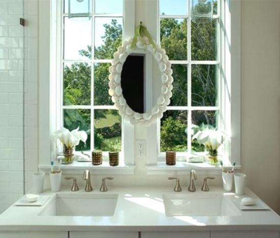 Oglinda ovala cu rama lata alba atarnata la fereastra de la baie