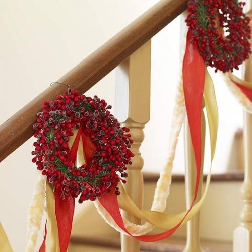 Coronite din fructe de merisor si panglici colorate atarnate de balustrada scarii