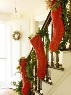 Hol cu scara interioara alba cu balustrada de lemn impodobita cu ciorapei rosii de Craciun