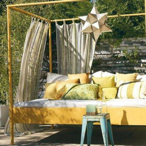 Pat de exterior cu perne decorative si perdea bej pentru un decor de terasa modern