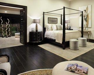 Dormitor amenajat in stil mediteranean cu zugraveala alba si parchet si mobila maro inchis