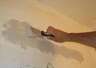 Aplicare glet cu spaclul pe peretele din baie