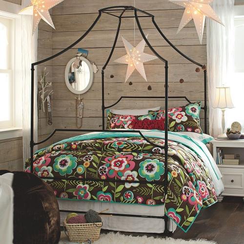Cuvertura cu flori coloarte asezata pe patul cu baldachin
