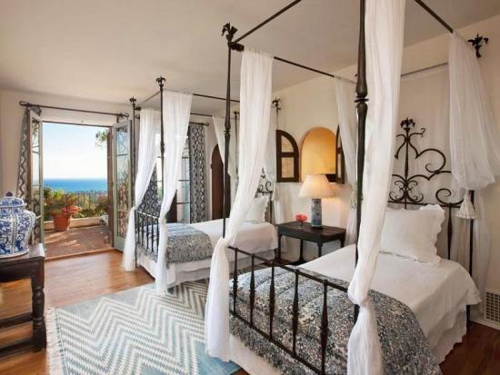 Dormitor pentru doi copii amenajat cu paturi din fier forjat cu baldachin