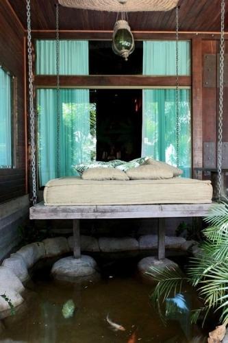 Amenajarea unei terase mici cu pat suspendat desupra unui lac artificial cu pesti
