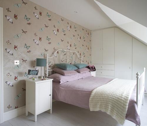 Camera la mansarda amenajata pentru o fetita cu pat din fier alb si tpet cu fluturi